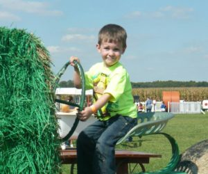 Boy driving straw tractor