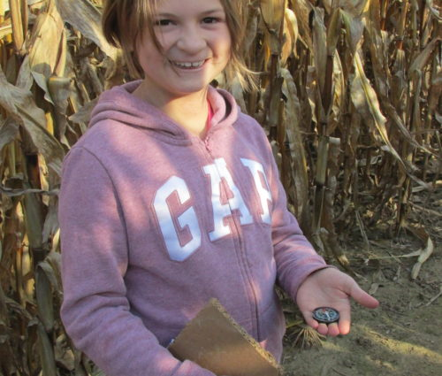 Girl with compass in corn maze